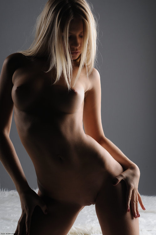 Cute tiny blonde is posing nude to the camera